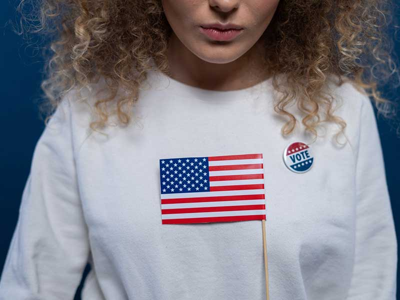 person holding an american flag and wearing a shirt pin that reads vote