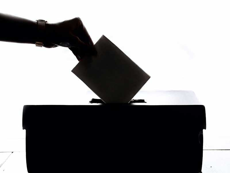 a hand putting a ballot in a box